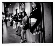 "La Paraditas (Young ones who stand against the wall). Young prostitutes, many from Mexico's impoverished rural south and Central America, line up for selection of passing male customers during midday, in the La Coahuila red light district, which is just a couple of hundred meters from the border fence, Tijuana, Mexico.  Some of the women who fail to make the crossing to the US for work end up here as prostitutes. Prostitution is legal in Tijuana and limited to three ""zones of tolerance""."