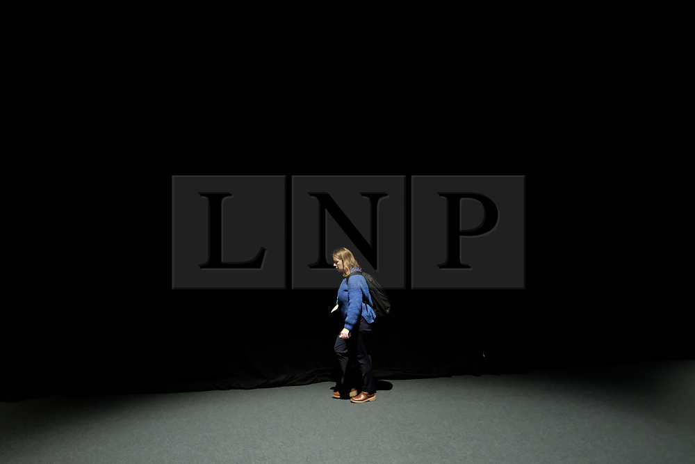 © Licensed to London News Pictures. <br /> 01/10/2017 <br /> Manchester, UK.  <br /> <br /> A woman walks behind long curtains back stage during the Conservative party Conference held in the Manchester Central Convention Complex.<br /> <br /> The conference will offer a schedule of speeches, receptions and fringe events giving a chance for party members and the public to learn about party ideas and policies for the year ahead.<br /> <br /> Photo credit: Ian Forsyth/LNP