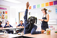 A student raises her hand in her art class at the Mother Caroline Academy and Education Center.