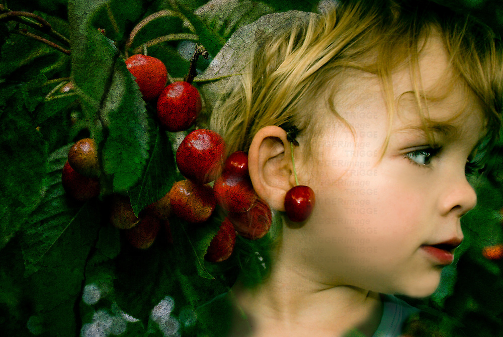 A young girl with blonde hair and red cherries