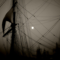 Dark silhouettes of sailing and sailing linen in the darkness under the moon.