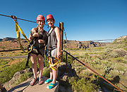 Two girls smiling while zip lining with the Perrine Bridge beyond in the Snake River Canyon with Zip the Snake in Twin Falls, Idaho.