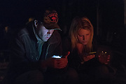 Couple on their cell phones by a fire pit, drinking apple cider.