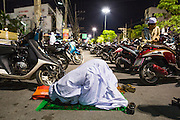 11 JULY 2013 - PATTANI, PATTANI, THAILAND:   Women pray among parked motorcycles in the street in front of the Pattani Central Mosque in Pattani, Thailand, Thursday night for Ramadan services. The mosque is one of the busiest in south Thailand. About 15,000 people attend nightly Ramadan services in the mosque. The crowd is so large it spills out of the mosque and onto the streets around it. Ramadan is the ninth month of the Islamic calendar, and the month in which Muslims believe the Quran was revealed. Muslims believe that the Quran was sent down during this month, thus being prepared for gradual revelation by Jibraeel (Gabriel) to the Prophet Muhammad. The month is spent by Muslims fasting during the daylight hours from dawn to sunset. Fasting during the month of Ramadan is one of the Five Pillars of Islam.    PHOTO BY JACK KURTZ