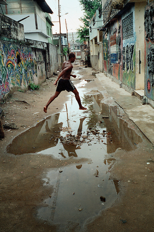 A jump to a more positive future? The colourful graffiti on the walls of the Afro Reggae centre have been painted by the favela children themselves. Vigario Geral, Rio de Janerio, Brazil. 2001