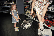 A young girl holds her mother's shopping basket while she tries on sandals in a department store in central Budapest, on 18th June 1990, in Budapest, Hungary.