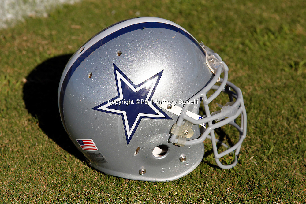 A Dallas Cowboys helmet lays on the grass during NFL football training camp on Wednesday, August 18, 2010 in Oxnard, California. (©Paul Anthony Spinelli)