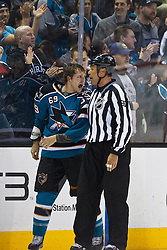 Feb 8, 2012; San Jose, CA, USA; San Jose Sharks center Andrew Desjardins (69) is escorted to the penalty box by NHL linesman Jay Sharrers (57) for fighting during the second period against the Calgary Flames at HP Pavilion. Calgary defeated San Jose 4-3. Mandatory Credit: Jason O. Watson-US PRESSWIRE