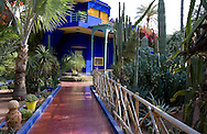 A cobalt blue pavilion surrounded by cactuses and palm trees in the Majorelle Garden, Marrakech, Morocco