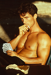 Good looking shirtless man with playing cards and smoking