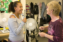 Day Service user with learning disabilities singing and being encouraged by the Day Service Officer,