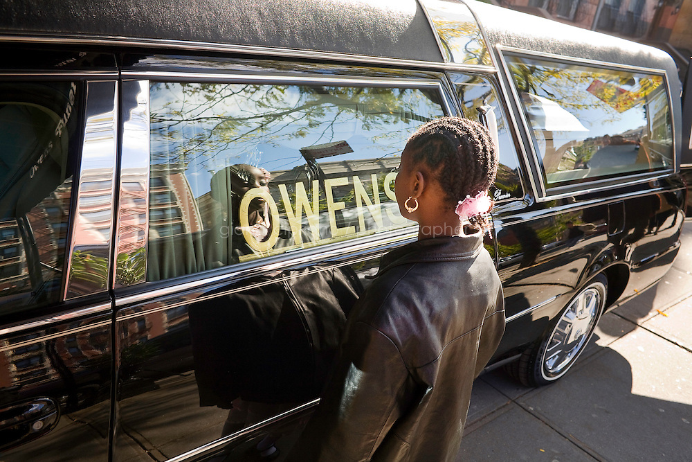 Harlem, New York, USA - November 7. A young girl observes the casket of her relative Doreen Guyton, which is placed the hearse ready to leave for the cemetery on November 7, 2007 in Harlem, New York, USA.