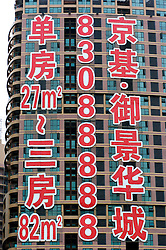 Large advertising sign on side of new apartment building under construction for sale in Shenzhen China