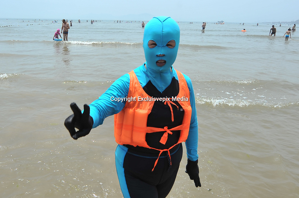 QINGDAO, CHINA - JULY 05: <br /> <br /> A woman wearing facekini is seen at beach on July 5, 2016 in Qingdao, Shandong Province of China. People wear the facekinis to protect themselves from sun\'s rays, jellyfish and algae.<br /> &copy;Excluisvepix Media