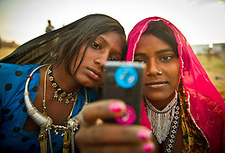 Sunita Devi, 13, left and Subita Devi, 13 take a photo with their mobile phone at the world's largest annual cattle fair in the desert town of Pushkar, in the Indian state of Rajasthan. Every year thousands of camel herders from the semi-nomadic Rabari tribe, who make a living rearing animals, travel for two to three weeks across 500 kilometers to set up camp in the desert dunes near Pushkar to sell their livestock. The herders sell more than 20,000 camels, horses and other animals at the annual cattle fair.