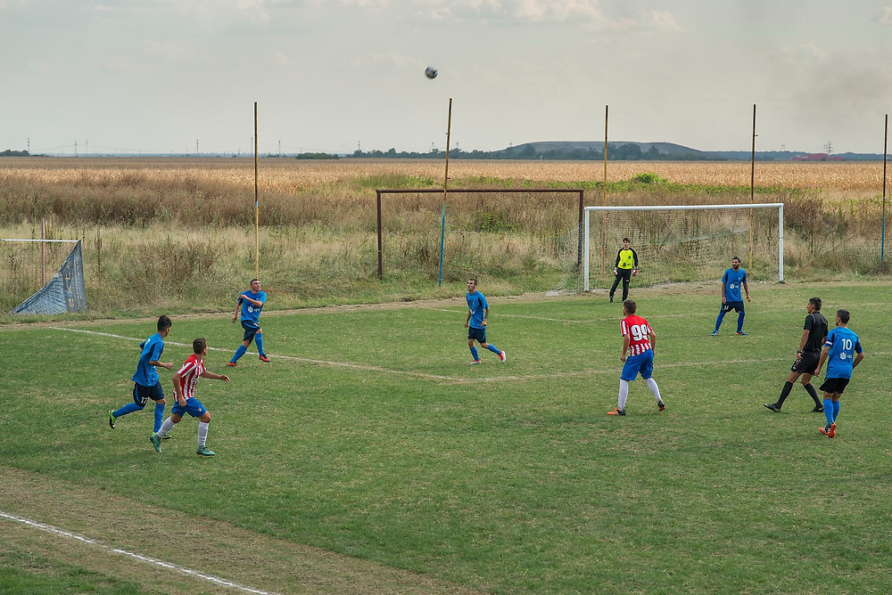 A football match from the IV, and lowest, division. In the background is a mound formed by waste at the city's main rubbish dump.
