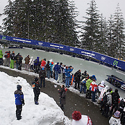 "Winter Olympics, Vancouver, 2010.Spectators find vantage points to watch the action during the Bobsleigh Four-man competition  at The Whistler Sliding Centre, Whistler, during the Vancouver Winter Olympics. 25th February 2010. Photo Tim Clayton..'BOB'..Images from the Four-man Bobsleigh Competition. Winter Olympics, Vancouver 2010..History was made at the Whistler Sliding Centre when the USA four-man bobsleigh team, led by Steven Holcomb took the Gold. The first time since 1948, a gap of 62 years, since the USA have won an Olympic Bobsleigh gold and they did it with their sleigh named ""Night Train""...The four days of practice and competition show the tension, nervousness and preparation as the teams of hardened men cope with the challenge of traveling at average speeds of over 150 km an hour. Indeed, five teams had already pulled out of the event before the opening heats because of track complexity, speed and fear, and on the final day, another four teams did not start after six crashes in the first two heats...Teams warm up behind the start complex, warming muscles in the cold in preparation for the explosive start. Many teams prepare in silence, mentally preparing themselves as they wait at the top of the run, in the bobsleigh sheds and the loading areas for their turn. When it's time to slide each team performs it's own starting ritual, followed by the much practiced start out of the blocks for just over four seconds, the teams are then in the hands of the accomplished drivers as they hurtle down the track for just over fifty seconds...Spectators clamber for the best position on track to see the sleighs for a split second, many unsuccessfully try to capture the moments on camera, The rumble of the sleigh is heard then the crowds gasp as it hurtles past in a blur...The American foursome of  Steven Holcomb, Justin Olsen, Steve Mesler and Curtis Tomasevicz finished with a pooled four-heat time of 3min 24.46sec. The German team led by Andre Lange won the Silver Medal"