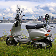 Silver 2003 Vespa ET-4 scooter with Seattle, Washington skyline in distance across Elliott Bay