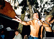 Man singing into his water bottle, Ibiza 1999
