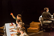 Brooklyn, NY - 11 December 2019. A performance of In Many Hands in BAM's Fishman Space, by Kate McIntosh in collaboration with Arantxa Martinez and Josh Rutter; sound design by John Avery; lighting design by Joëlle Reyms. The piece involves participants sitting at 3 long, narrow tables, with facilitators at each end, and either passing along objects—here a sealed container of yellow liquid and a red gelatinous blob—or repeating hand movements in the manner set by a facilitator.
