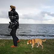 Nederland Den Oever Zurich 22 november 2008 20081122 Foto: David Rozing ..Serie afsluitdijk. De Afsluitdijk is een belangrijke waterkering en verkeersweg in Nederland. De waterkering sluit het IJsselmeer af van de Waddenzee. Hieraan ontleent de dijk zijn naam. De verkeersweg, onderdeel van Rijksweg a7, verbindt Noord-Holland met Friesland...Vrouw laat haar hond uit op afsluitdijk tijdens stormachtig weer. Guur weer, koud, wind, waaien, winderig, hard, harde, uitwaaien, hondje, verwaaien, frisse neus halen, herfst, herfstig, hondje uitlaten, weersomstandigheden, klimaat,  deltaplan..Foto David Rozing