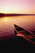 Classic wooden canoe on calm lake at sunset.