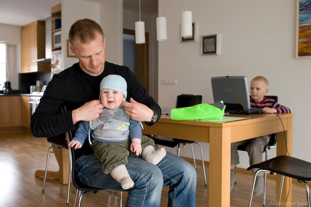 Hafsteinn Halldórsson (35) with his son Dagur (6 months) at home. Older son Máni (6) in background.