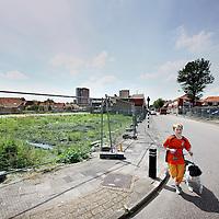 Nederland, Zaandam , 14 juni 2010..Kruispunt bij rosmolenstraat in Rosmolenwijk waar een aantal woningbouwprojecten van corporatie Parteon stil staan...Housing projects of the Parteon corporation have been stalled. A boy in orange is walking his dog.