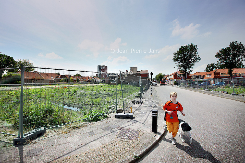 Nederland, Zaandam , 14 juni 2010..Kruispunt bij rosmolenstraat in Rosmolenwijk waar een aantal woningbouwprojecten van corporatie Parteon stil staan...Housing projects of the Parteon corporation have been stalled. A boy in orange is walking his dog.