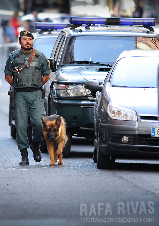 A Spanish Civil Guard officer and a police dog patrol outside a flat in in the northern Spanish Basque city of Bilbao during an operation against Basque separatist group ETA on July 22, 2008. Photo Rafa Rivas