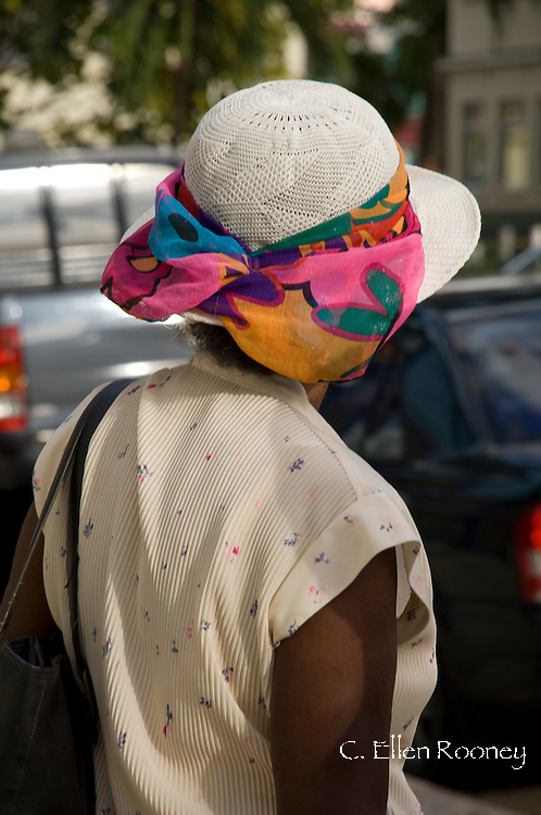 A woman wearing a straw hat with a colourful band in Castries, St Lucia, The Windward Islands, The Caribbean