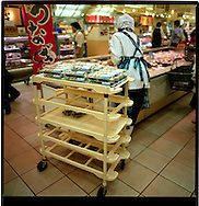 Clerk puts packaged maki roll sushi into cooled display cases in a Tokyo department  store, Japan.