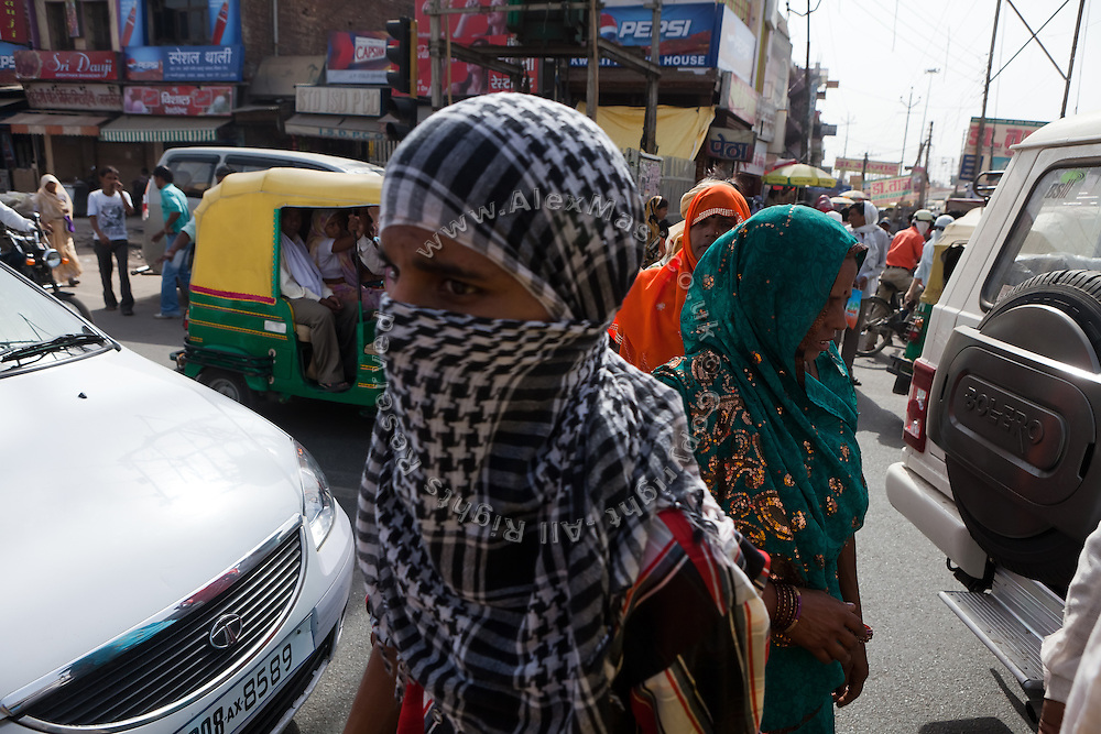 People are walking on the streets of Agra, next to a busy junction. The Taj Mahal has been struggling to keep in shape also because of the high levels of pollution in the city, mainly caused by congested roads and high levels of traffic, vehicles and an increasing population, in Agra.
