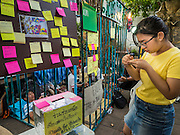 "06 JULY 2015 - BANGKOK, THAILAND:  A person writes a ""Post It"" note in support of arrested university students during a protest at Thammasat University. More than 100 people gathered at Thammasat University in Bangkok Monday to show support for 14 students arrested two weeks ago. The students were arrested for violating orders against political assembly. They face criminal trial in military courts. The students' supporters are putting up ""Post It"" notes around Bangkok and college campuses up country calling for the students' release.     PHOTO BY JACK KURTZ"