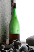 old wine bottle with molding passion fruit and stones near window