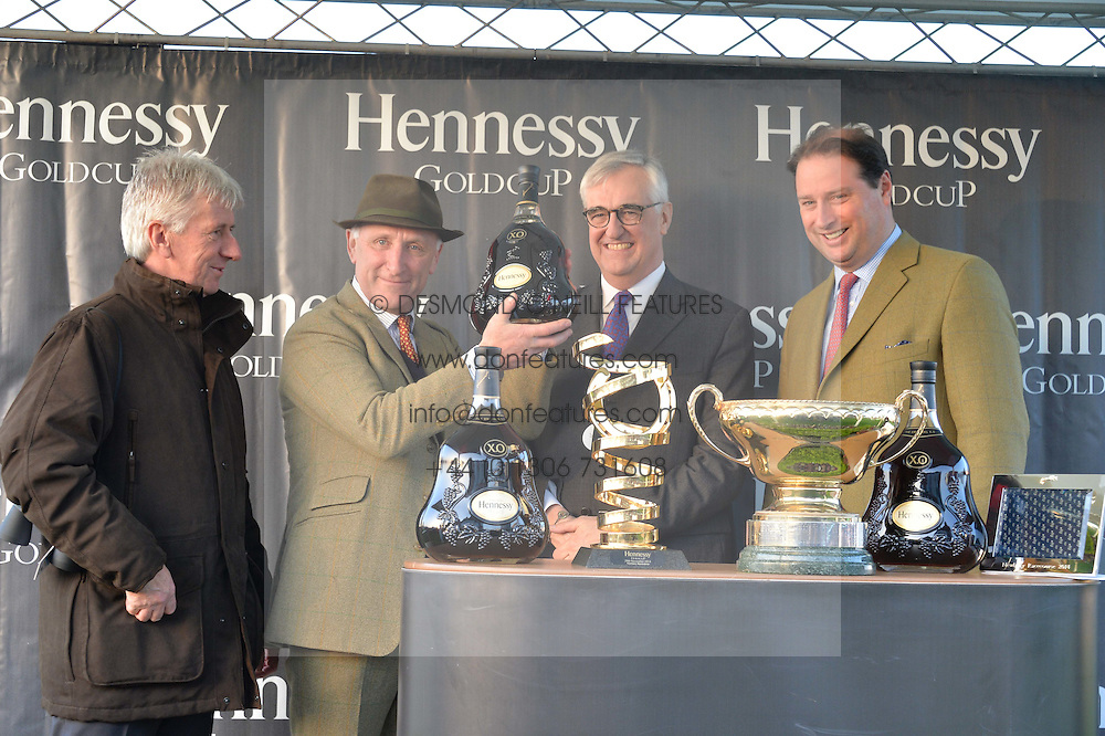 Left to right, ?, trainer OLIVER SHERWOOD, MAURICE HENNESSY and JO THORNTON at the 2014 Hennessy Gold Cup at Newbury Racecourse, Newbury, Berkshire on 29th November 2014.  The Gold Cup was won by Many Clouds ridden by Leighton Aspell.