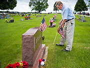 25 MAY 2020 - ROLAND, IOWA: GLENN KAPPELMANN places an American flag on the grave of a family member in Roland Cemetery, in Roland, Iowa, a farming community an hour north of Des Moines. In 2020, most public Memorial Day events in Iowa were canceled because of the COVID-19 pandemic, but some families had their own private events. Kappelmann was participating in a private family ceremony with the Ritland family, from Roland. Memorial Day is a federal holiday to honori and mourn the military personnel who have died while serving in the United States Armed Forces. Memorial Day is observed on the last Monday in May.       PHOTO BY JACK KURTZ