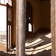 Looking into a sand-filled home through a broken window, in Kolmanskop, Namibia