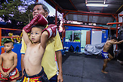 "18 DECEMBER 2104 - BANGKOK, THAILAND: A boy who wants to box watches a sparring session at the Kanisorn gym. The Kanisorn boxing gym is a small gym along the Wong Wian Yai - Samut Sakhon train tracks. Young people from the nearby communities come to the gym to learn Thai boxing. Muay Thai (Muai Thai) is a Thai fighting sport that uses stand-up striking along with various clinching techniques. It is sometimes known as ""the art of eight limbs"" because it is characterized by the combined use of fists, elbows, knees, shins, being associated with a good physical preparation that makes a full-contact fighter very efficient. Muay Thai became widespread internationally in the twentieth century, when practitioners defeated notable practitioners of other martial arts. A professional league is governed by the World Muay Thai Council. Muay Thai is frequently seen as a way out of poverty for young Thais and Muay Thai camps and schools are frequently crowded. Muay Thai professionals and champions are often celebrities in Thailand.     PHOTO BY JACK KURTZ"
