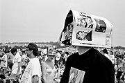White male stands with NME magazine on his head, behind him is a large crowd of people. Glastonbury 2000