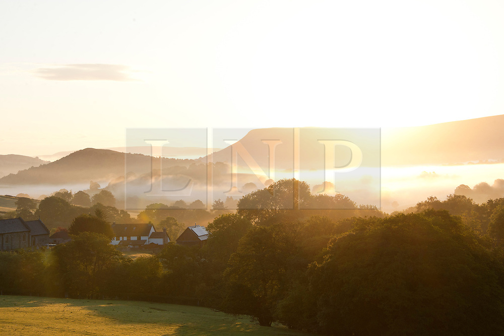 © Licensed to London News Pictures. 04/05/2019. Llanddewi'r Cwm, Powys, Wales, UK. Mist surrounds the small Welsh village of Llanddewi'r Cwm in Powys. After a very cold night with temperatures dropping to 3 deg C in Powys, the valleys are filled with early morning mist. Photo credit: Graham M. Lawrence/LNP