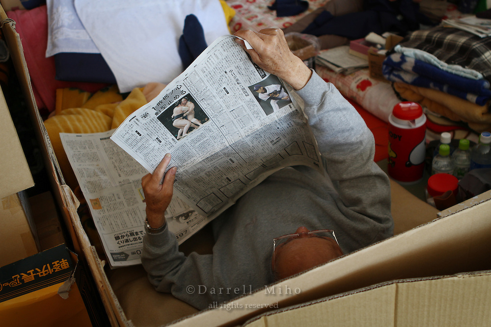 May 18, 2011; Minamisanriku, Miyagi Pref., Japan - 1:19 p.m. After lunch, an evacuee reads the newspaper in his living space at the Shizukawa High School Evacuation Center in Minamisanriku after the magnitude 9.0 Great East Japan Earthquake and Tsunami that devastated the Tohoku region of Japan on March 11, 2011.
