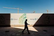 ABU DHABI, EMIRATS ARABES UNIS - 20 JANVIER 2016: Un homme passe devant un site en construction à Masdar City. Le projet final devrait s'étendre sur 6 kilomètres carrés et accueillir 45000 personnes.