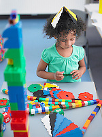 Girl playing with shape puzzles in classroom elevated view