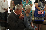 An elderly man kisses the hand of his new bride.