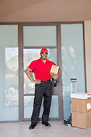 Portrait of a happy young delivery man standing with packages