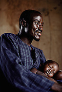 Soumana Natomo holds one of his children as she naps.  The Natomo family lives in two mud brick houses in the village of Kouakourou, Mali, on the banks of the Niger River. They are grain traders and own a mango orchard. According to tradition Soumana is allowed to take up to four wives; he has two. Wives Pama and Fatoumata are partners in the family and care for their many children together. Material World Project.