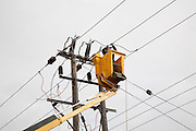 Electrician working in cherry picker connecting high voltage power lines at Bucklesham, Suffolk, England