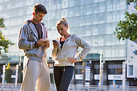 Young couple standing while using smartphone after working out