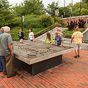 Visitors at Williamsburg Visitors Center look at large map of the historic complex.